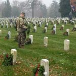A soldier laying wreaths
